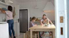 Parents Helping Children With Homework At Kitchen Table Stock Footage