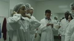 4K Workers in clean room prepare to start work on factory floor Stock Footage