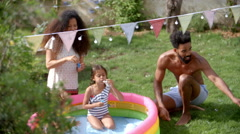 Overhead View Of Family Having Fun In Garden Paddling Pool Stock Footage