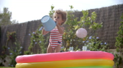 Girl Having Fun In Garden Paddling Pool Stock Footage