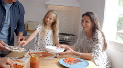 Family At Home In Kitchen Making Pizzas Together Stock Footage