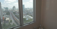 In the city of Bangkok, Thailand young girl in apartment by window taking a bath Stock Footage
