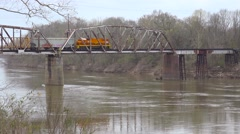 A freight train travels over a trestle over a river in the deep south. Stock Footage