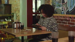 African American woman browsing on digital tablet at pizza place - 4K Stock Footage