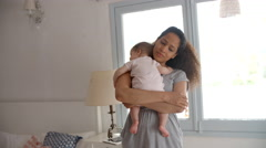 Mother Cuddling Baby Daughter At Home In Front Of Window Stock Footage