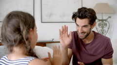 Father And Daughter Playing Clapping Game Sitting On Sofa Stock Footage