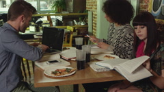 Three friends working or studying at pizza place - 4K Stock Footage