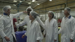 4K Production facility team staff together on factory floor Stock Footage