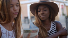Three female friends looking at a guidebook outside a cafe Stock Footage
