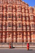 Local people walking in front of Hawa Mahal in Jaipur, Rajasthan, India. Stock Photos