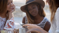 Three female friends read guidebook outside a cafe, close up Stock Footage
