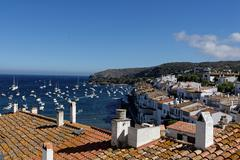 Over the roofs of Cadaques overlooking the Badia de Cadaques. Stock Photos