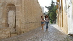 Two female friends walk through old Ibiza with a guidebook Stock Footage
