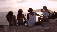 Group Of Friends Sit On Cliff Watching Sunset Shot On R3D Stock Footage