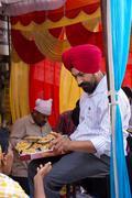 Indian man giving away rice at Guru Nanak Gurpurab celebration during communi Stock Photos