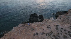 Aerial Shot Of Friends On Cliffs Watching Sun Set Over Sea Stock Footage