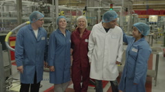 4K Production facility team staff together on factory floor. Stock Footage