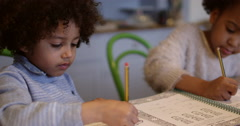 Two Children Doing Homework At Kitchen Table Shot On R3D Stock Footage