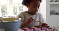 Girl Putting Mixture Into Cake Cases With Father Shot On R3D Stock Footage