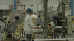 4K Worker applies labels to products. Pharmaceutical manufacturing facility Stock Footage