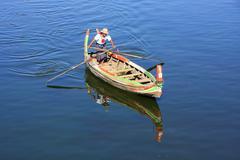 Local man in a boat at sunset, Amarapura, Myanmar Stock Photos
