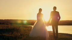 Bride and groom running through the field to meet the sun at sunset Stock Footage