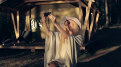 Woman in a Poncho and Hat Photographs on the Phone Next to the Tent Stock Footage