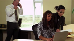 Three coworkers working together on laptop Stock Footage