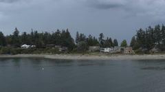 POV-Passing houses on Bainbridge Island shoreline on overcast day Stock Footage