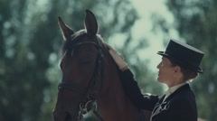 Elegant woman rider in a long frock coat and hat petting horse Stock Footage