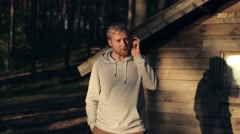 Man Talking on the Phone Next to a Wooden House in the Woods Stock Footage