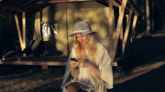 Woman in a Poncho and Hat Sitting With a Phone Next to the Tent Stock Footage