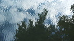 Abstract reflection in rippling water of cloudy sky and tree overhead Stock Footage