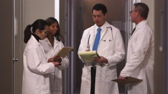 A group of doctors standing in the hallway talk and take notes and then look up Stock Footage