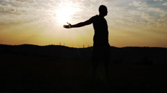 Silhouette of a Man in the Background of the Sun Spreads His Arms to the Sides Stock Footage