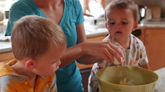 A mother making a cake with her little boys in the kitchen dolly shot Stock Footage
