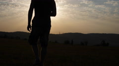 Silhouette of a Man Goes Into the Mountains to the Sun Stock Footage