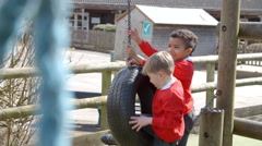 School Pupils On Tire Swing At Breaktime Shot On R3D Stock Footage