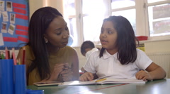 Teacher Helps Female Pupil With Work In Class Shot On R3D Stock Footage