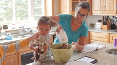 A mother making cake with little boys in a kitchen dolly shot Stock Footage