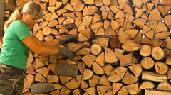 Young woman lays on chopped wood in the woodpile Stock Footage