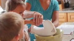 A mother making cake with little boys in the kitchen dolly shot Stock Footage