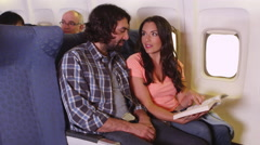 Couple reading book on plane Stock Footage