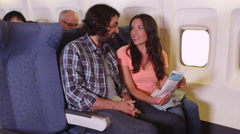 Couple reading pamphlet on plane Stock Footage