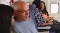 Couple drinking water bottle on plane Stock Footage