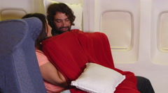 Passengers using blanket and pillows on plane Stock Footage