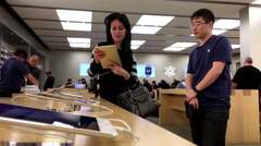 Woman asking questions about ipad inside Apple store with 4k resolution. Stock Footage