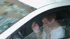 Sad man crying in the car. rain on the street. man in hysterics Stock Footage