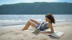 A beautiful sexy young lady is laying at a beach using laptop Stock Footage