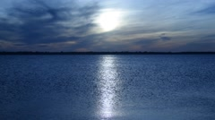 Panorama of enormous sun disk and sun-path across tranquil sea against defocused Stock Footage